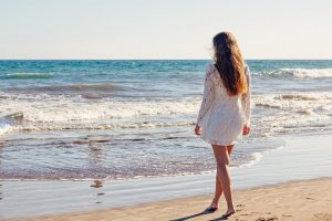 woman on the beach thinking about the reasons to never leave Long Island.