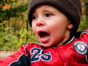 A kid in a red jacket crying.