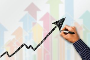 Hand drawing an arrow that shows a rise, like you will do once you boost your profits.