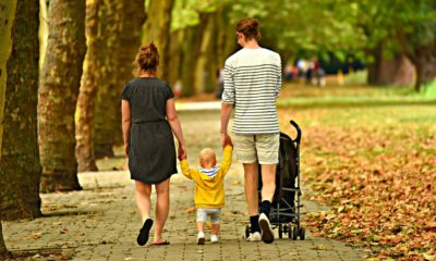 Parents with two small kids walking and talking, just like you would when thinking about how to make your relocation simple for your kids.