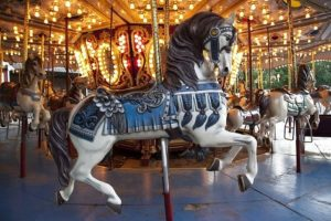 Carousel with horses and various colorful lights.