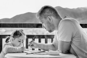 Father and daughter drawing and talking.
