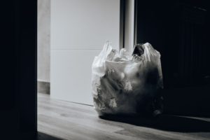 Garbage in a plastic bag next to a door.
