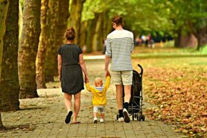 Parents walking their son in the park.