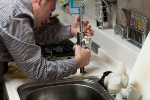 A plumber fixing a kitchen tap