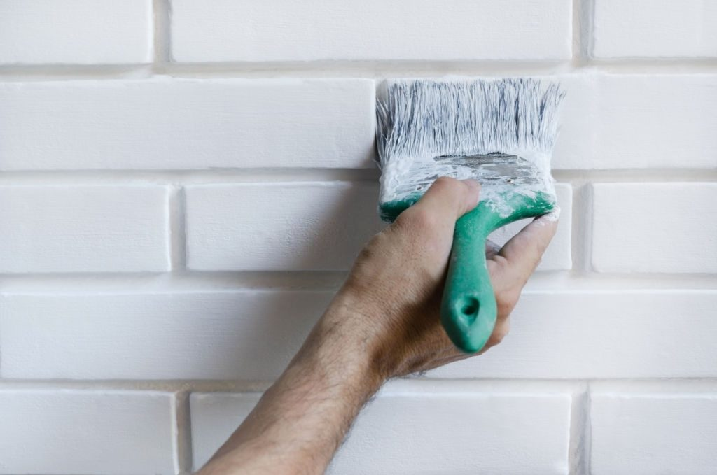 Man painting with brush brick wall on white color, close-up