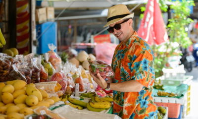 an expat buying fruits in the fresh market in Thailand